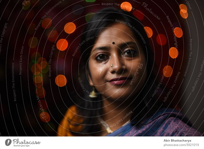 Face portrait of a smiling Indian woman in light bokeh background adult art asian beautiful bengali celebration cheerful clothing culture diwali celebration