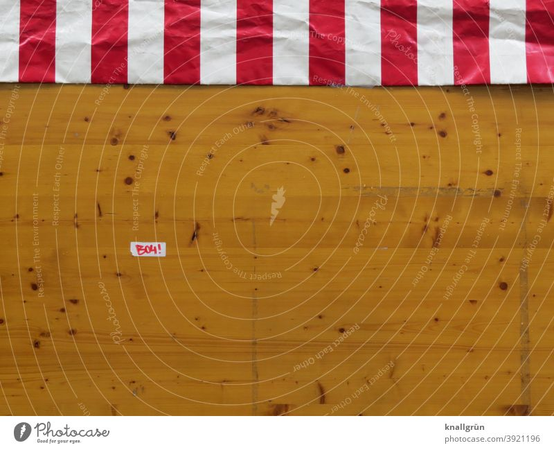 Back of a market stall with striped tarpaulin and small sticker Market stall stickers Striped Reddish white Wood boards Knotholes Colour photo Brown White