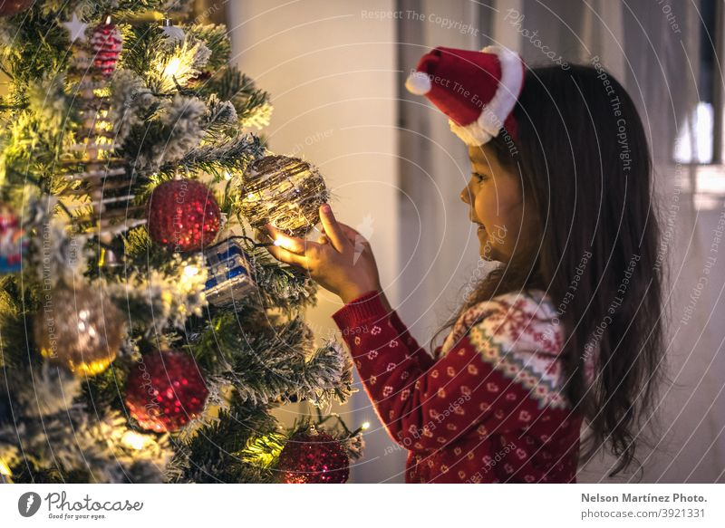 Little girl dressed in a Christmas sweater and a Christmas hat, hanging the Christmas balls on the tree. nice open beautiful magic background portrait woman box