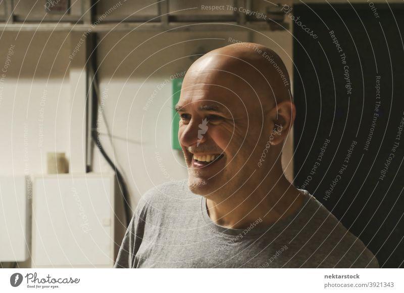 Bald Headed Man Smiling in Garage Background man bald caucasian worker workshop diy no hair 1 person garage background handiwork industrial machine shop