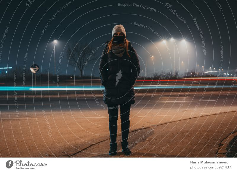 woman with mask and winter clothing standing on the street while car lights passing behind, time moving concept active activity adult background beautiful