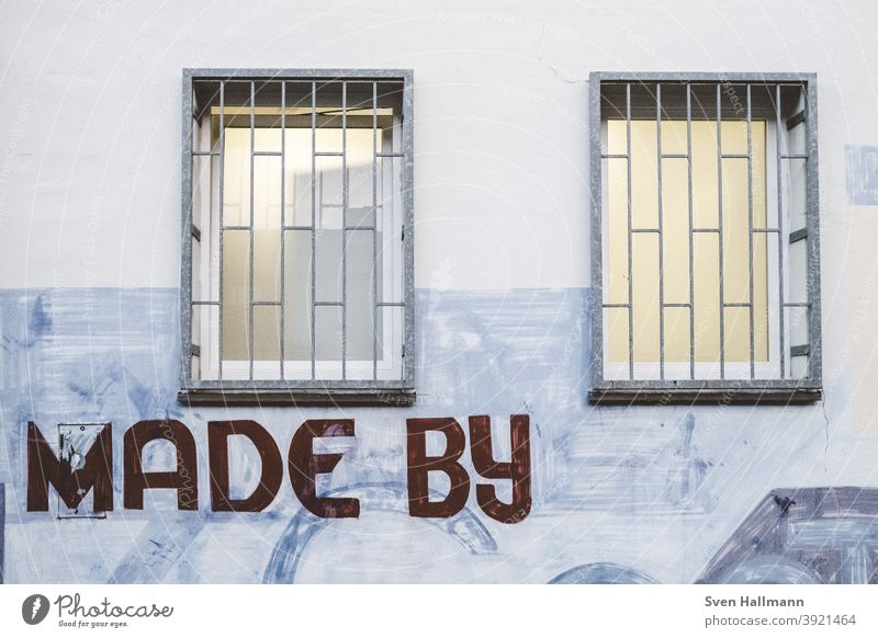 Graffiti on wall with windows Made by urban Window Grating Exterior shot Facade Wall (building) Deserted Colour photo Town Characters Architecture