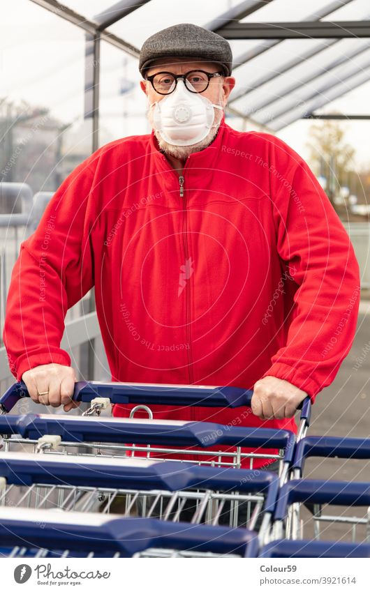 Man wears an mask while pushing a shopping cart new normal grandpa covid epidemic face mask 2019-ncov protective infection buyer one man only look groceries
