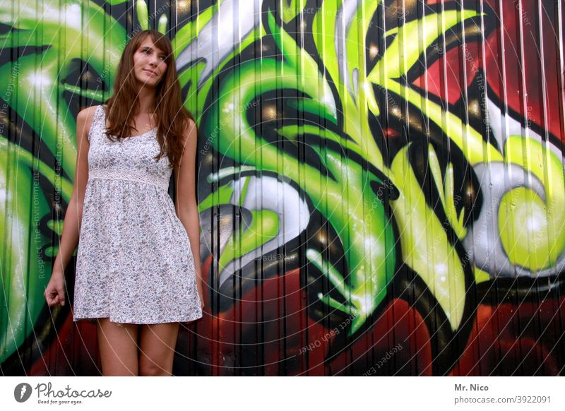 Young woman stands in front of a graffiti wall and looks shyly to the left Summer dress Wall (building) Art Characters Street art Facade Woman Long-haired