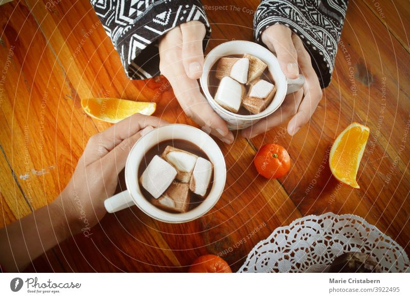 Sharing a cup og hot chocolate drinks with marshmallow on the Christmas morning new years eve togetherness human connection holiday marshmallows traditional