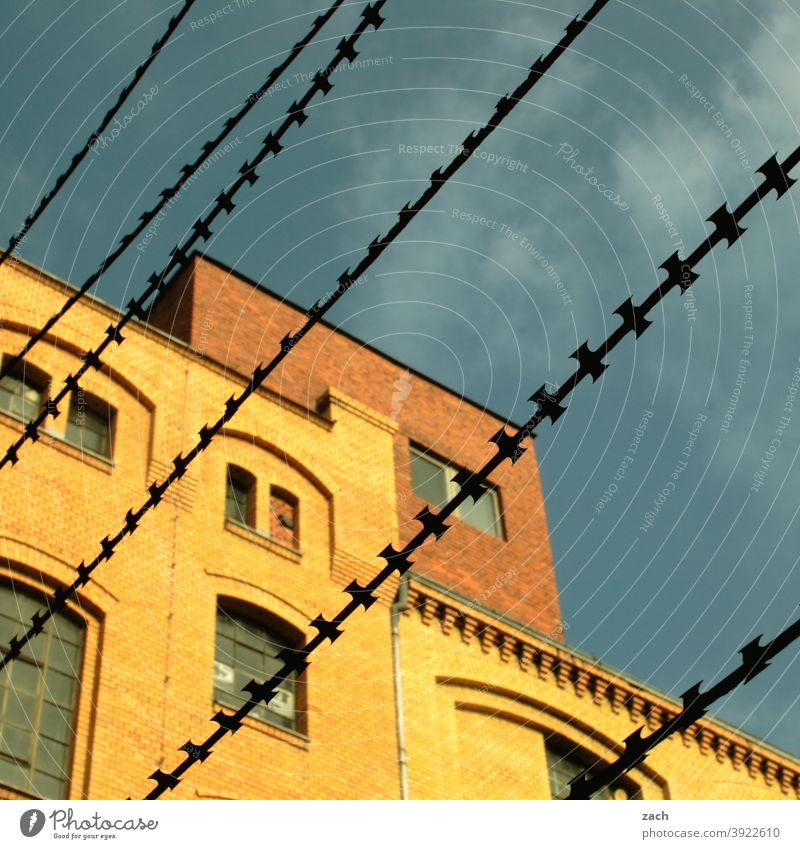 behind bars House (Residential Structure) Barbed wire Barbed wire fence Grating Brick facade Brick-built house Yellow Diagonal Line Fence Captured Protection