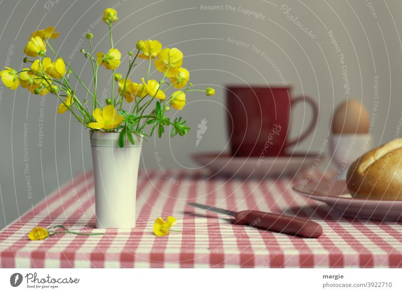 A vase with buttercups stands on a breakfast table with a red checked tablecloth. A roll on a plate with a knife, in the background a red cup on a saucer and a boiled egg in an egg cup