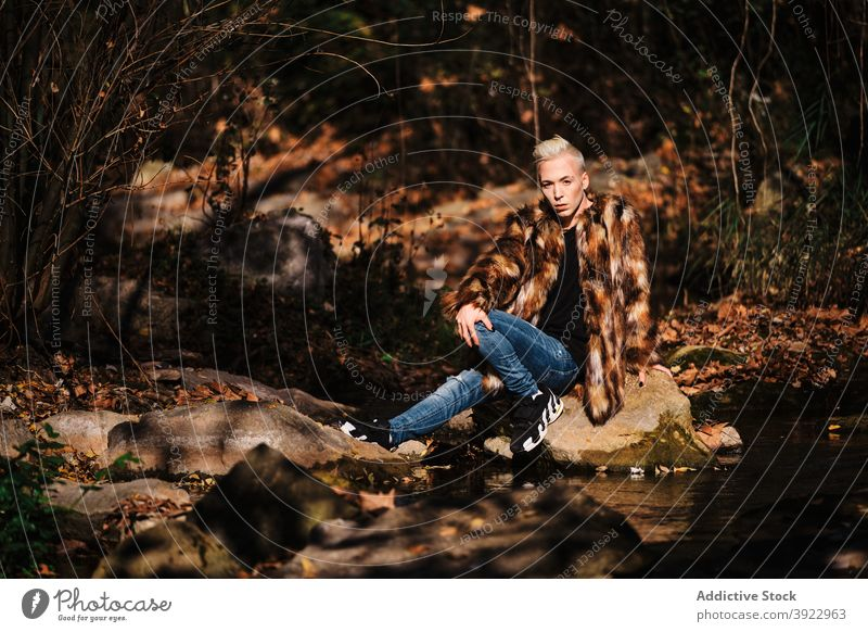 Stylish transgender man in fashionable outfit sitting in autumn forest lgbt style fur young blond nature coat alternative male homosexual gay lifestyle lgbtq