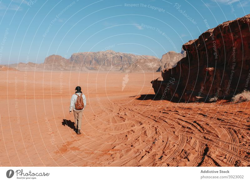 Anonymous traveler standing in desert with mountains during vacation sandstone valley explore tourist arid dry nature wanderlust wadi rum jordan outerwear