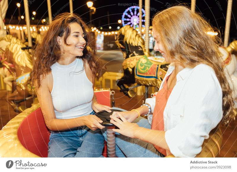 Joyful girlfriends riding carousel on funfair having fun ride happy cheerful laugh together enjoy young female summer evening lifestyle friendship excited