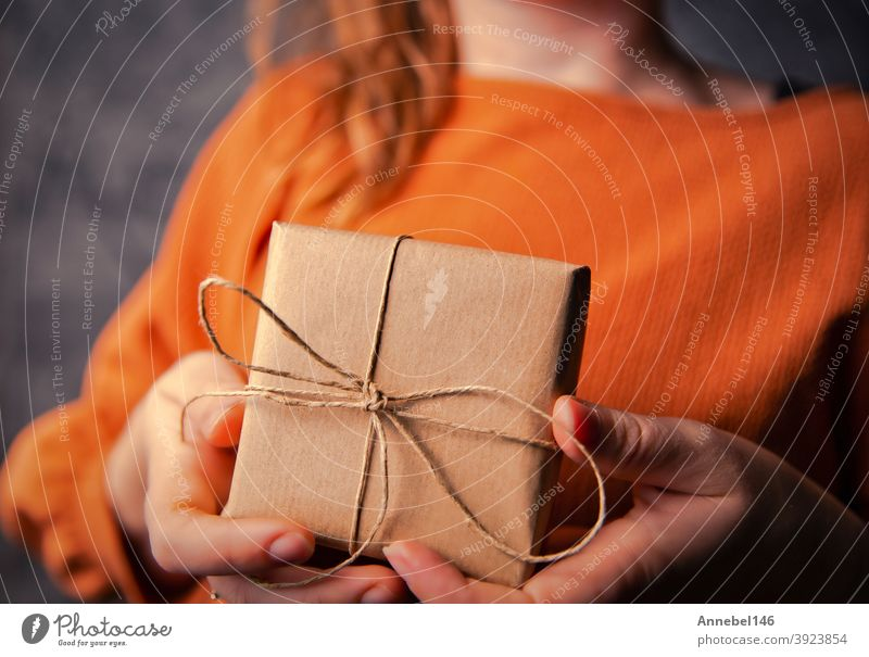 Young Female holding a kraft gift box, wrapped in plain brown paper, Valentines day, Birthday, Mothers Day present or gift concept selective focus, dark background