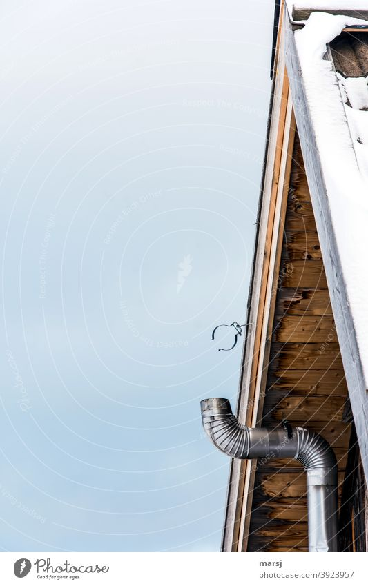 The pipe clamp at the gable of a simple hut waits for the completion of the stovepipe or at least for a meaningful use Stovepipe Heating pipe pipe clip Ice