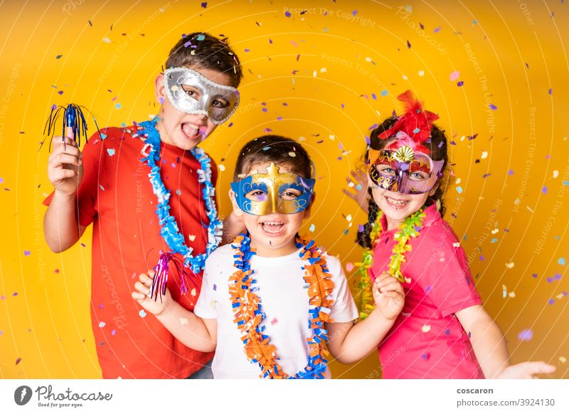 Three kids celebrating Carnival or New Years Eve at home background beautiful birthday boy cap carnival celebration cheerful child childhood children clothing