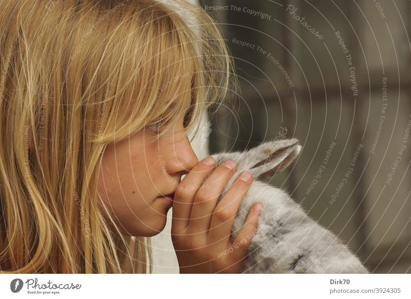 Portrait of a young girl with rabbit in profile Girl Girlish Girl`s face Profile Meditative reflectiveness tranquillity quiet scene tender tenderness