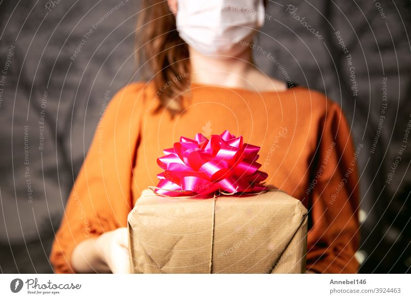 Young Female holding a kraft paper gift box with pink decoration with medical protective face mask for Coronavirus, Covid-19 and present concept. Birthday or Valentines day retro design