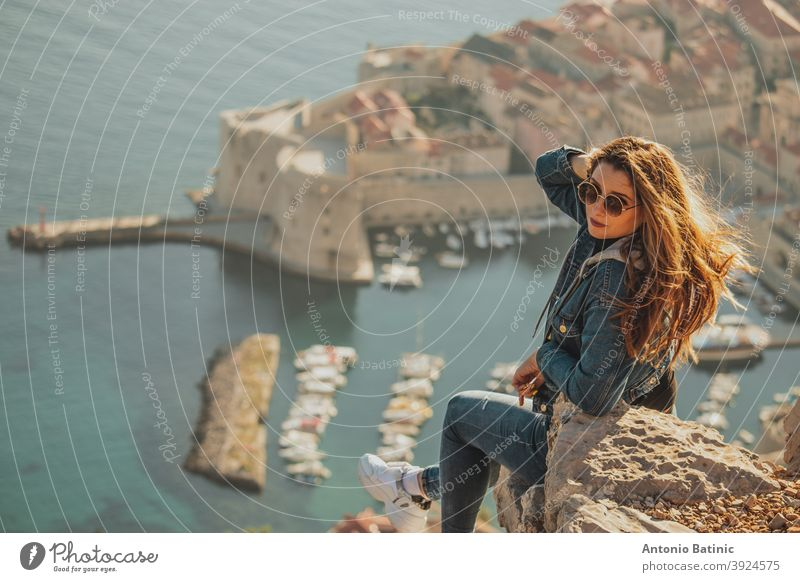 Attractive brunette seen from behind posing while sitting on a stone above the city of Dubrovnik, outlines of the majestic old town in the background. Traveler visiting the walls and the Srd mountain