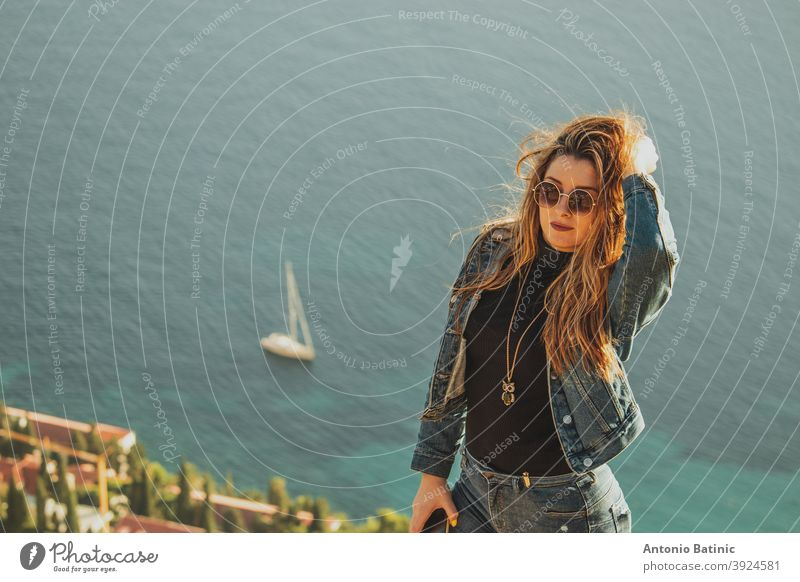 Portrait of an attractive brunette with sunglasses posing sensually with the bright blue adriatic sea behind her. Small sailboat on the sea near Dubrovnik, concepts of travel with copyspace room
