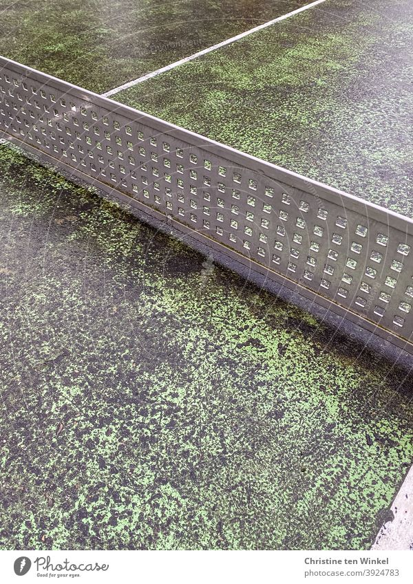 Old and worn grey green outdoor concrete table tennis table with 'net' made of solid plastic grid Table tennis table Table tennis net worn-out Partition