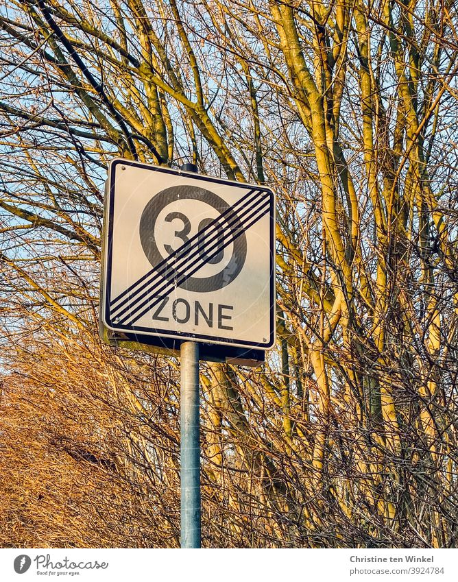 30 zone end, traffic sign in front of bare bushes 30 mph zone Road sign Road traffic Transport Signs and labeling Traffic infrastructure Signage Safety Street