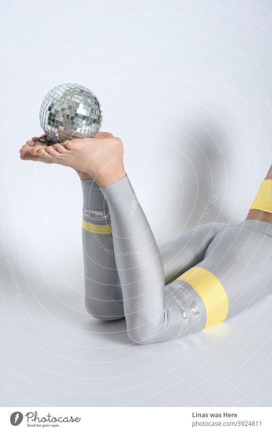 Long legs are perfect for a women sports fashion studio shoot. An accent to this image is a small disco ball, though these shiny grey tights are an accent themselves.