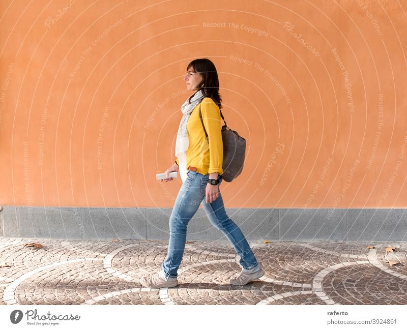 Side view of a backpacker traveler walking against orange wall in the city woman street outdoor person urban 1 holiday maker brunette lady vacation trip tourism