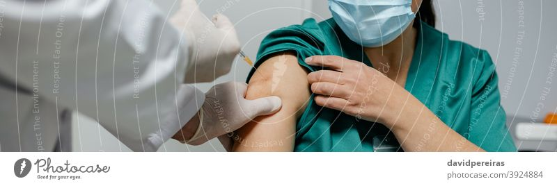 Female surgeon receiving coronavirus vaccine health personnel injection priority group doctor covid-19 banner web header panorama panoramic arm clinic medicine