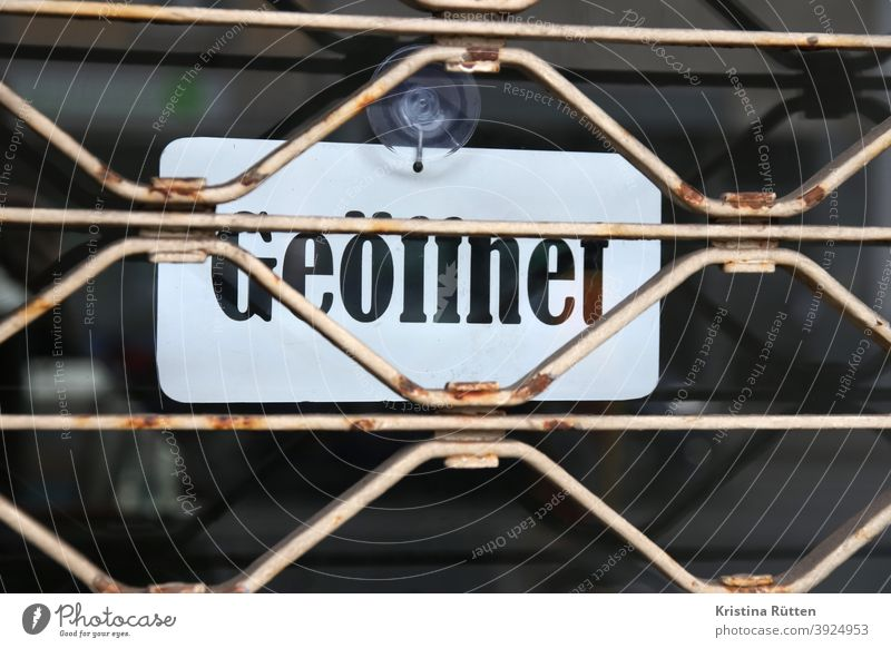 open sign behind closed rolling grille Notice roller grilles Grating Closed locked too Conflicting Disagreement door Entrance opening hours Opening time