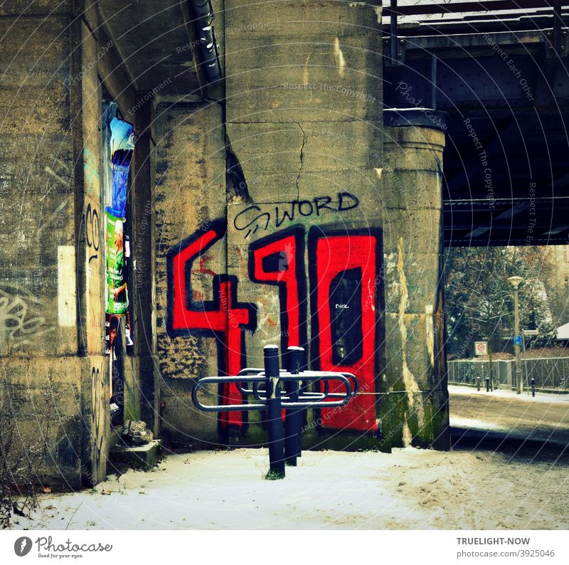 Through wild Babelsberg in winter with dirty snow, a railway underpass, bold blood red graffiti numbers 490 and S word written black on grey concrete pillar, empty bike stand, street, garden fence, lantern