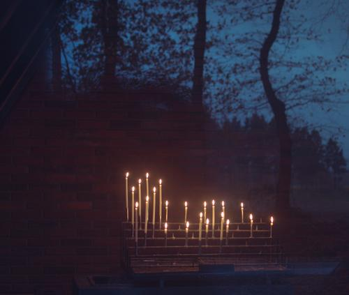 Candle altar with burning candles in a chapel, photographed through a glass door. It reflects trees and the evening sky at blue hour Sacrificial candles