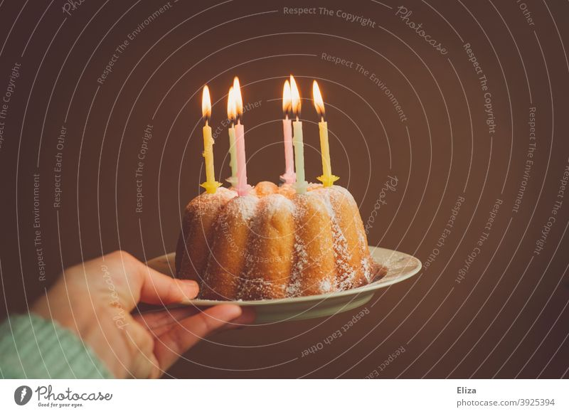 Hand holding a birthday cake with burning candles Birthday birthday candles Cake Happy Birthday Birthday celebration guglhupf Feasts & Celebrations