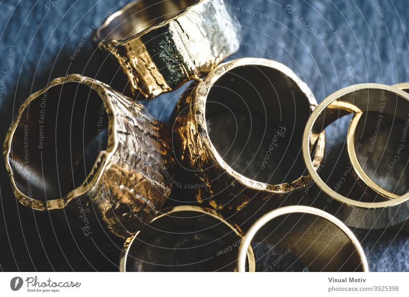Close-up of several golden rings piled on a slate board abstract detail close-up fashion chic shiny design metallic decorative objects bijou interior macro
