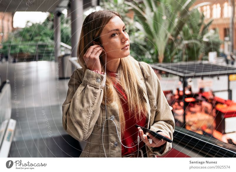 Young Girl With Headphones headphones girl portrait young 20s front view blonde pretty using phone cellphone caucasian looking standing woman female smartphone