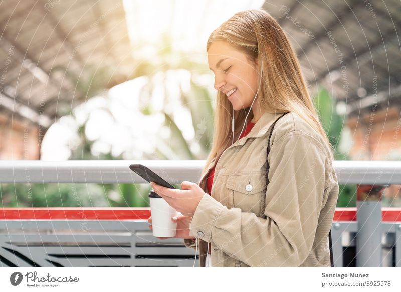 Smiley Girl Looking at Phone side view looking at phone cup of coffee headphones girl portrait young 20s blonde pretty using phone cellphone caucasian standing