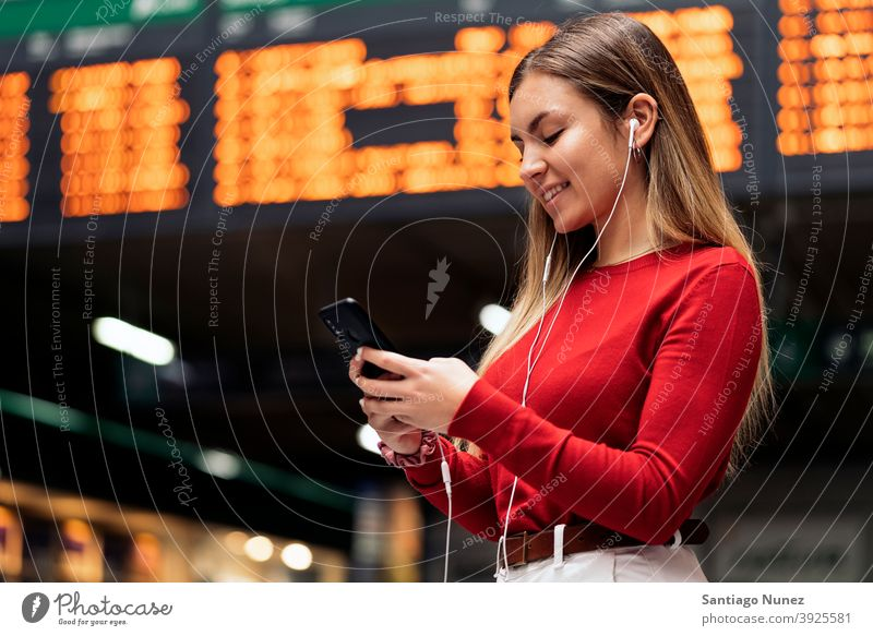 Girl in Train Station station train station side view looking at phone headphones girl portrait young 20s blonde pretty using phone cellphone caucasian standing