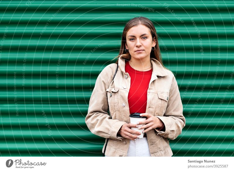 Pretty Young Girl Portrait portrait looking at camera cup of coffee green background standing pretty woman girl young female outside outdoors front view posing
