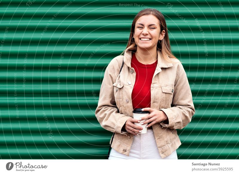 Happy Young Girl Portrait portrait looking at camera cup of coffee green background standing pretty woman girl young female outside outdoors front view posing