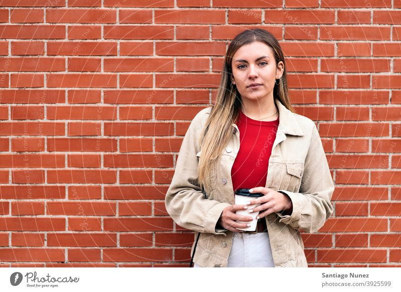 Young Girl Portrait portrait looking at camera cup of coffee wall standing pretty woman girl young female outside outdoors front view posing one person alone