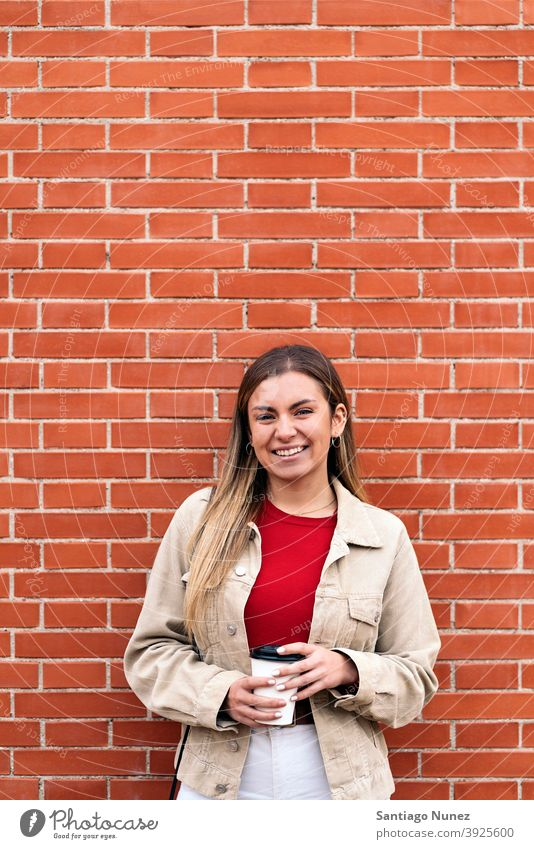 Young Girl Smiling Portrait portrait looking at camera cup of coffee wall standing pretty woman girl young female outside outdoors front view posing one person
