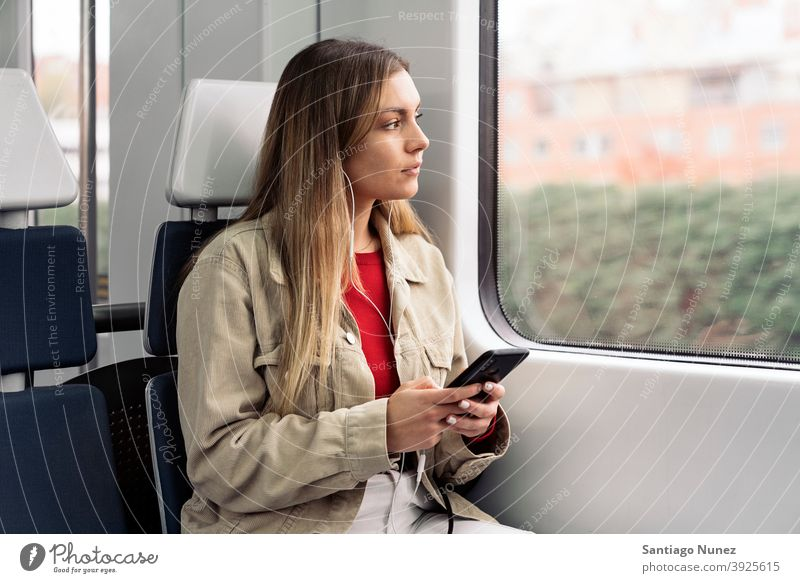 Blonde Girl in Train train traveling headphones girl portrait young 20s front view blonde pretty using phone cellphone caucasian looking standing woman female