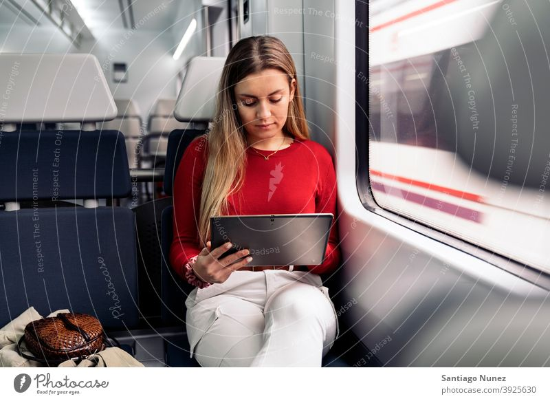Blonde Girl in Train tablet train traveling girl portrait young 20s front view blonde pretty using tablet caucasian looking standing woman female smartphone
