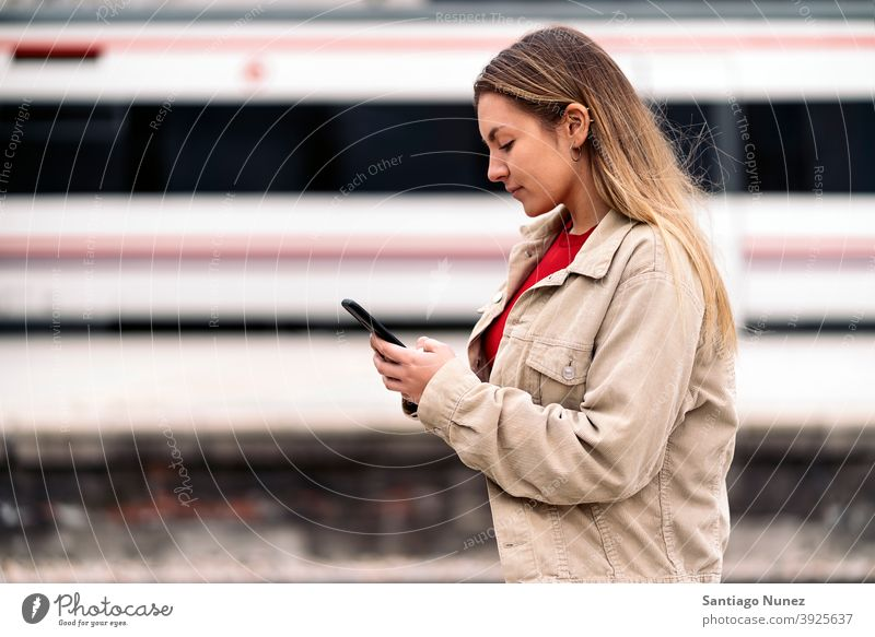 Blonde Girl Waiting For Train side view woman caucasian train motion portrait using phone typing looking background standing female outside outdoors metro
