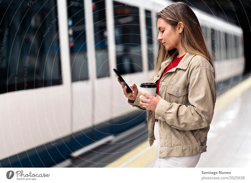 Blonde Girl Waiting For Train side view woman caucasian train motion portrait using phone typing looking background standing female indoors metro transport