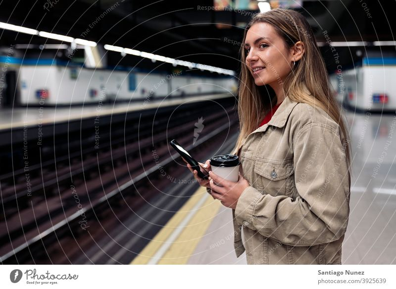 Young Girl Waiting in Train Platform side view woman caucasian train platform portrait using phone typing looking background standing female indoors outdoors