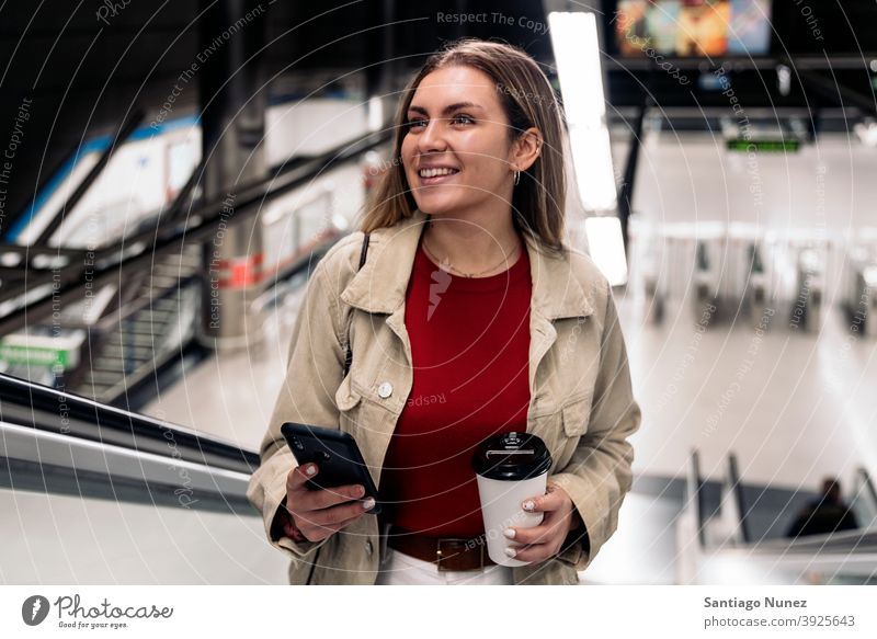 Happy Girl on Escalator stairs escalators station train station woman young girl cup of coffee phone using phone smiling front view smile portrait 20s blonde