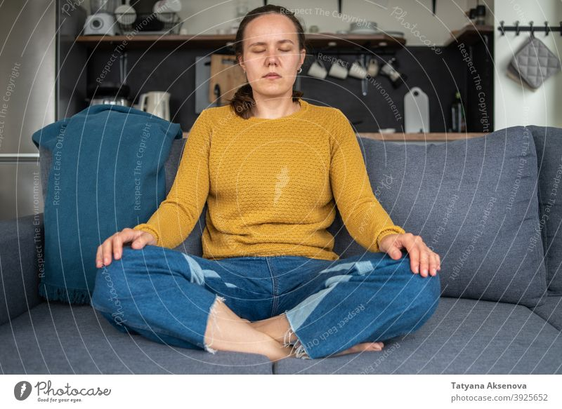 Woman practicing yoga at home woman meditating relaxation female sitting wellbeing wellness balance lifestyle person adult cross-legged exercising position