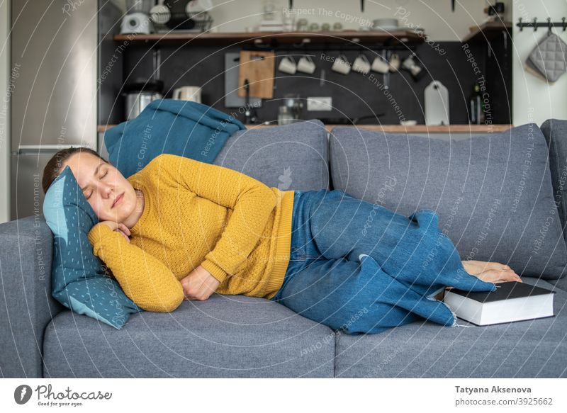 Woman sleeping after reading woman book indoor sofa home relaxation living room comfortable person female lifestyle caucasian adult leisure couch literature