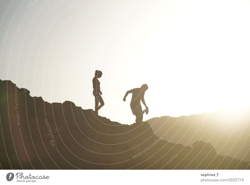 silhouette of couple walking downhill in backlight during sunset mountain vacation adventure hiking together summer sunrise woman climbing active walking home