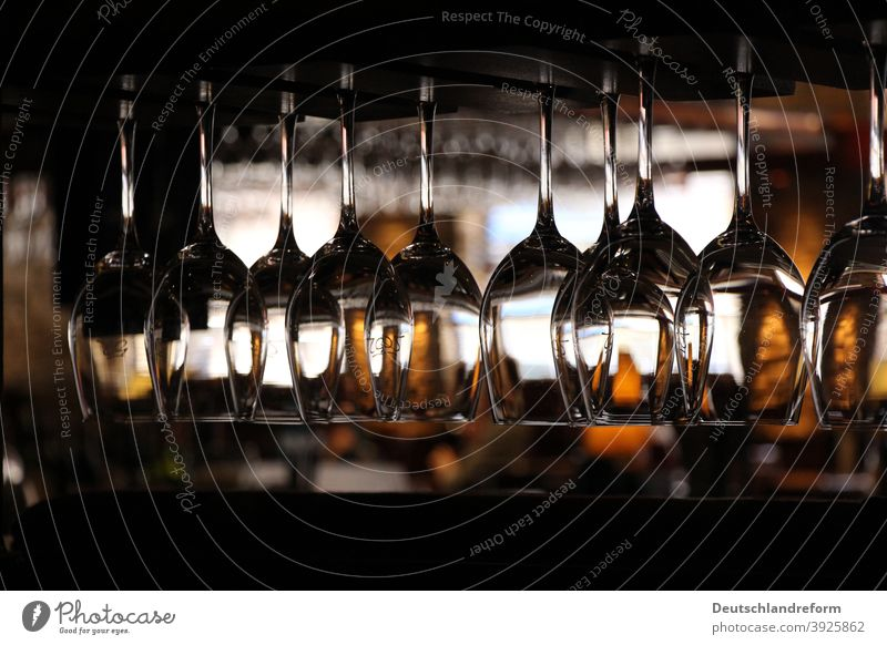 Close-up of wine glasses hanging on a shelf in dark surroundings of a restaurant Glass Light reflection Glasses structured Fragile Wine glass Vine Gastronomy