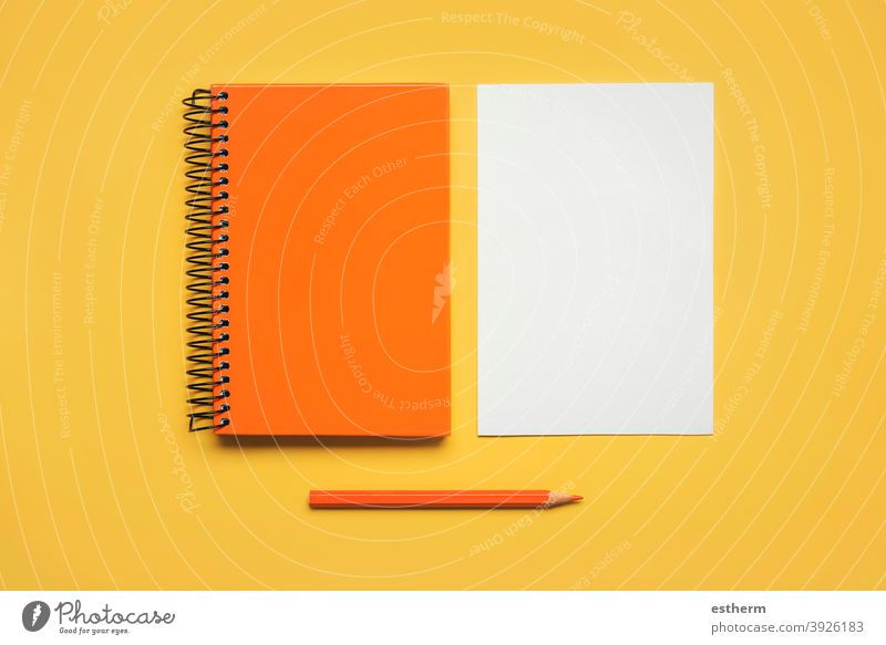 orange spiral notepad with a sheet of white paper and orange pencil color pencil back to school education memo space pages text notebook document student letter