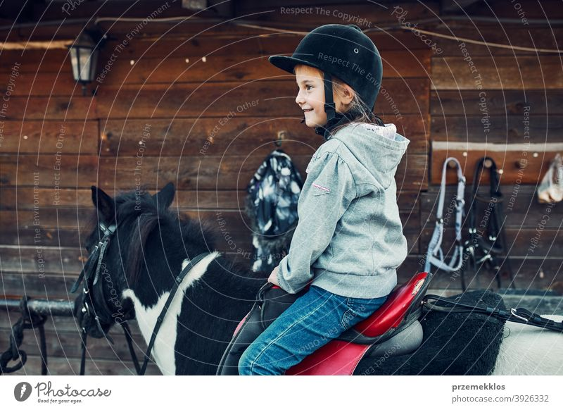 Little smiling girl learning horseback riding kid ride practice school cute country pretty rural ranch lesson rider happiness countryside active equestrian